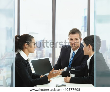 Young businesspeople having a business meeting in corporate office, using laptop computer. Copyspace on blank screen.