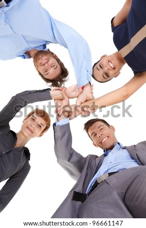 Young businesspeople linking hands, smiling, looking at camera, view from below.? - stock photo
