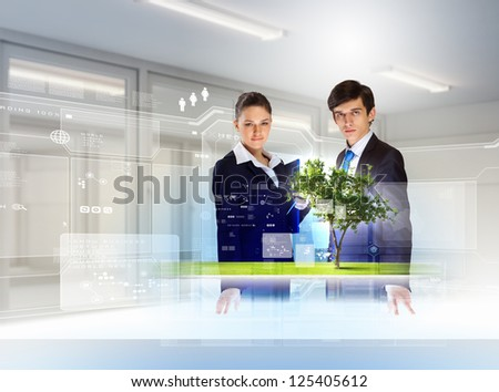 young businesspeople looking at high-tech image of tree - stock photo