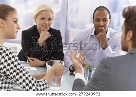 Young businesspeople sitting at a meeting having discussion. - stock photo