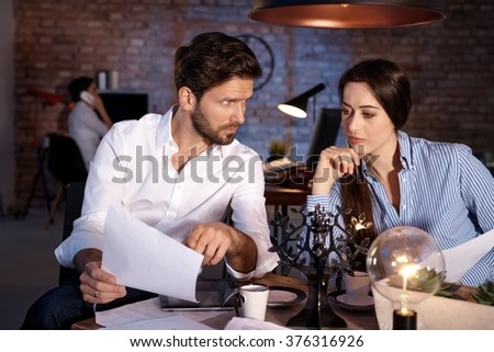 Young businesspeople sitting at desk, working together late. - stock photo