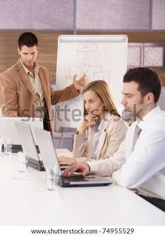 Young businesspeople sitting at meeting, using laptop and whiteboard.?
