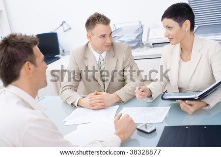 Young businesspeople sitting at office desk, having a business meeting. - stock photo