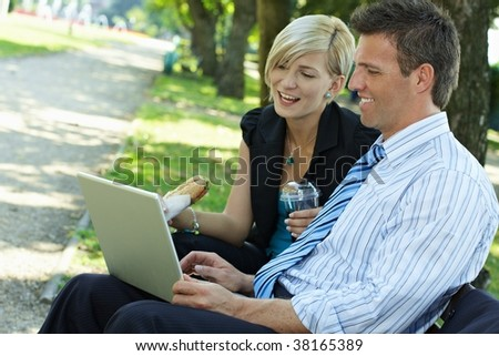 Young businesspeople sitting on bench in park having luch and looking at laptop computer. - stock photo