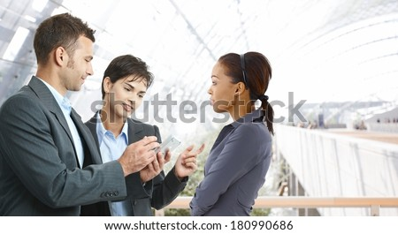 Young businesspeople talking at office lobby, using palmtop. - stock photo