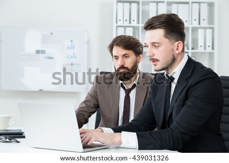 Young businesspeople with beards sitting at office desk and discussing business project on laptop - stock photo