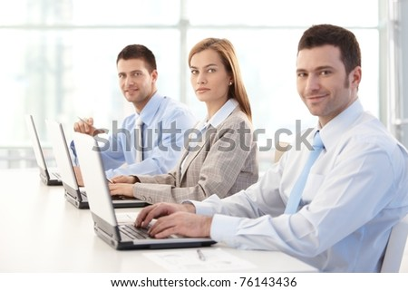 Young businesspeople working on laptop in bright office, smiling.? - stock photo