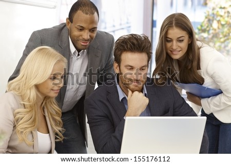 Young businesspeople working together in bright office, using laptop computer. - stock photo