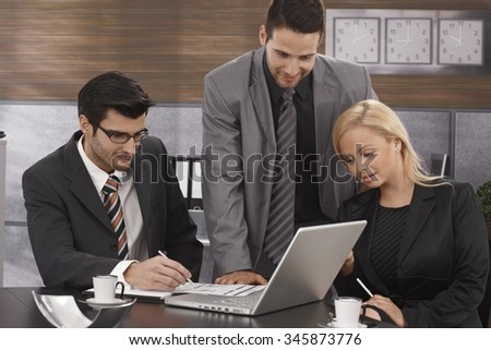 Young businesspeople working together in meetingroom, using laptop computer. - stock photo