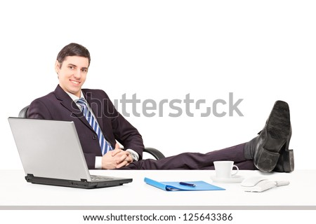 Young businessperson sitting in the office with his legs up isolated on white background - stock photo