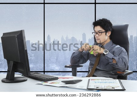 Young businessperson working at workplace while enjoy hot coffee near the window
