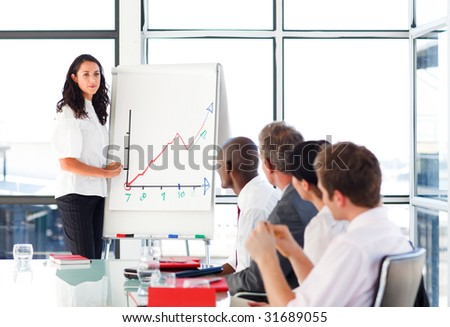 Young businessswoman reporting to sales figures in a meeting - stock photo