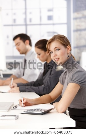 Young businessteam having a meeting, writing notes.? - stock photo