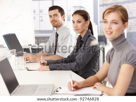 Young businessteam sitting at meeting table, listening presentation, writing notes.? - stock photo