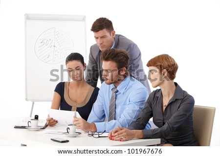 Young businessteam working on project in meeting room. - stock photo