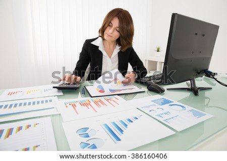 Young Businesswoman Analyzing Report On Chart With Calculator