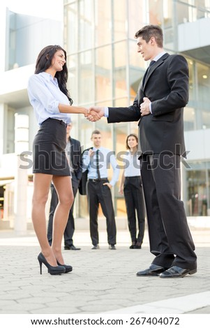 Young businesswoman and businessman shaking hands in front of the company while in the background standing theirs of the business team. - stock photo