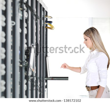 Young businesswoman and datacenter server room - stock photo
