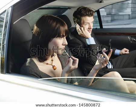 Young businesswoman applying lip gloss and businessman using cell phone in car - stock photo