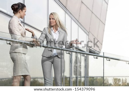Young businesswoman arguing with female colleague at office balcony - stock photo