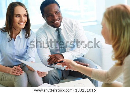 Young businesswoman asking her partners sign paper at meeting - stock photo