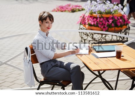 Young businesswoman at a sidewalk cafe - stock photo
