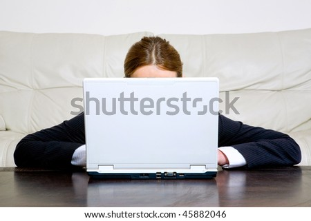 Young businesswoman behind laptop at the table - stock photo
