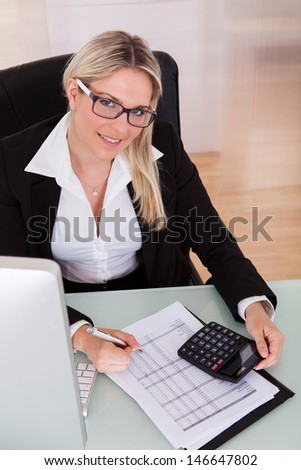 Young Businesswoman Calculating Data In Her Office - stock photo