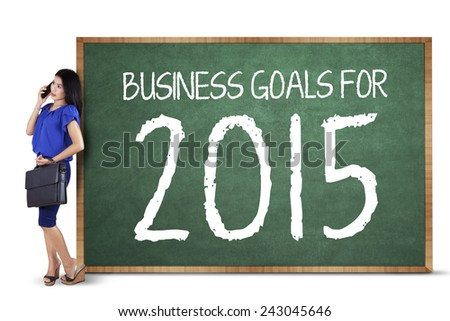 Young businesswoman calling with mobile phone while leaning on a board of business goals for 2015 - stock photo