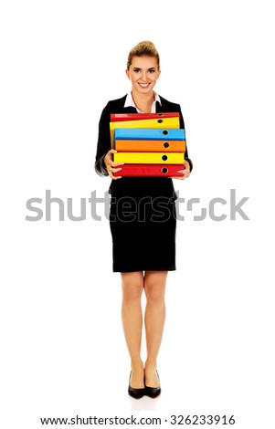 Young businesswoman carries heavy binders. - stock photo