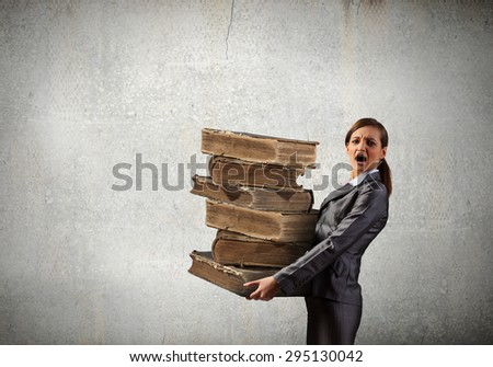Young businesswoman carrying pile of old books