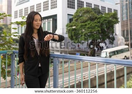 Young businesswoman checking time fot appointment in Hong Kong.  - stock photo