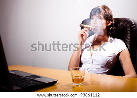 Young businesswoman chilling in her office, smoking a cigar and drinking whiskey