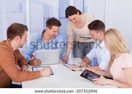 Young businesswoman discussing with colleagues during conference meeting - stock photo