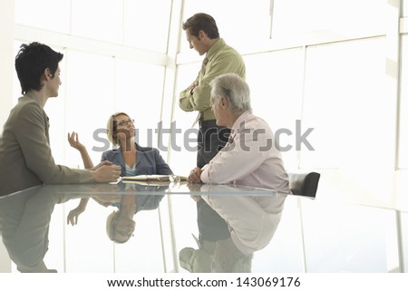 Young businesswoman discussing with colleagues in conference room - stock photo