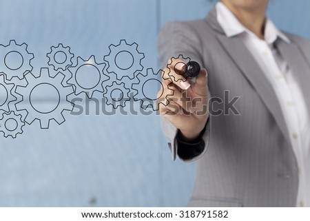 Young businesswoman drawing cogwheels on visual screen