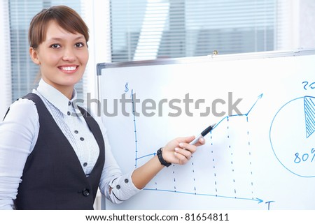 young businesswoman drawing graph on chart in office - stock photo
