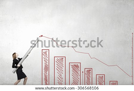 Young businesswoman drawing growing graph with huge pencil