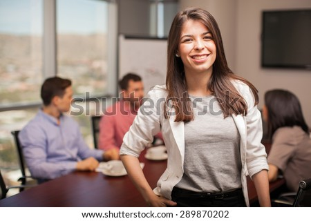 Young businesswoman dressed casually and smiling while her colleagues work on the background - stock photo