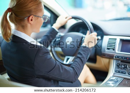 Young businesswoman driving car - stock photo