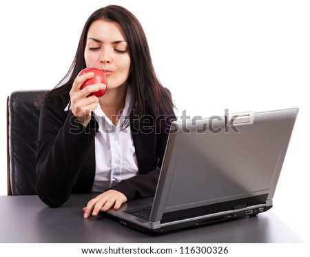 Young businesswoman eating an apple while sitting at office desk isolated on white background