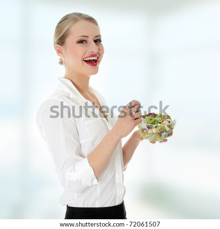 Young businesswoman eating salad - stock photo