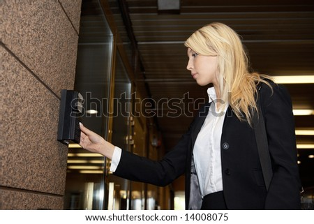 Young businesswoman entering access code at building entrance - stock photo