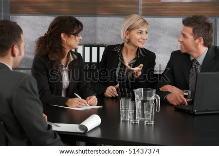 Young businesswoman explaining business problem, sitting at meeting table in office, others looking at her. - stock photo