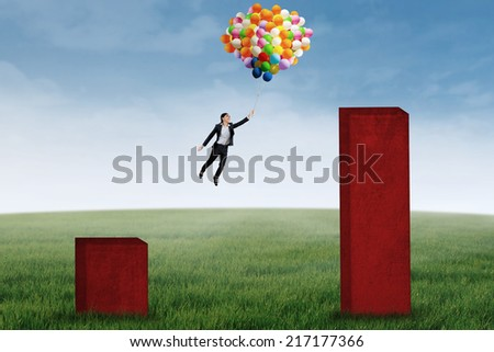 Young businesswoman flying with balloons over upward business chart - stock photo