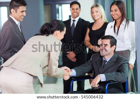 young businesswoman greeting handicapped business partner and team - stock photo