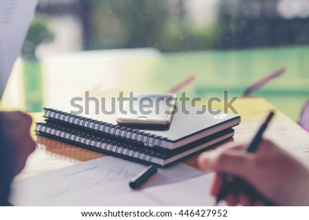 Young businesswoman hard at work at her desk writing notes on a pad from her laptop computer with analytical charts and graphs in front of her, high angle view - stock photo