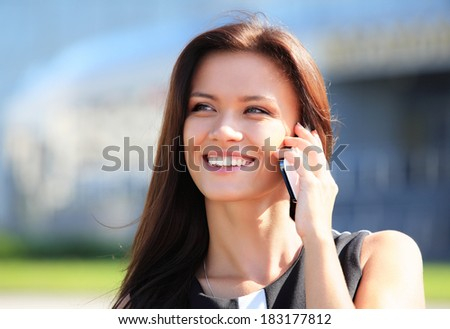Young businesswoman having a conversation using a smartphone on a phone call - stock photo