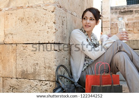 Young businesswoman having a lunch break and sitting down on a park steps with her shopping bags and bottle of water. - stock photo