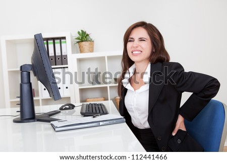 Young businesswoman having back pain while sitting at office desk - stock photo